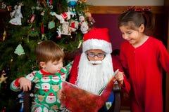 年轻圣诞老人读对孩子 库存照片