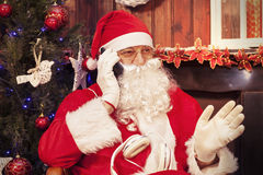 圣诞老人画象谈话与手机在他的家为 库存照片