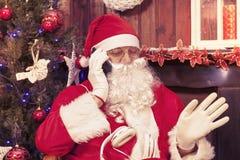 圣诞老人画象谈话与手机在他的家为 免版税库存图片