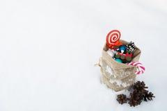 圣诞老人` s充分礼物袋子圣诞节玩具和礼物在雪 免版税库存图片