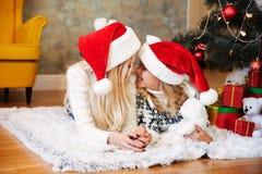 圣诞老人` s帽子和她的小女儿感人的eac的年轻母亲 免版税库存照片