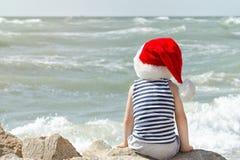 圣诞老人` s帽子和镶边T恤杉的男孩坐海滩 回到视图 免版税库存图片