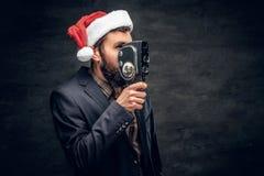 圣诞老人` s帽子的一个人拿着老8mm摄象机 免版税库存照片