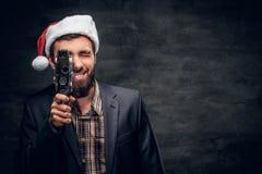 圣诞老人` s帽子的一个人拿着老8mm摄象机 库存照片