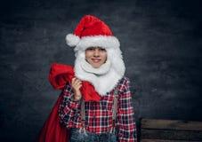 圣诞老人` s帽子的一个男孩拿着新年礼物大袋 免版税库存照片