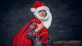 圣诞老人` s帽子的一个男孩拿着新年礼物大袋 库存照片