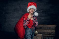 圣诞老人` s帽子的一个男孩拿着新年礼物大袋 库存图片