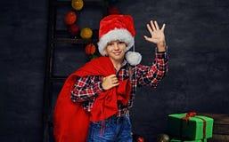 圣诞老人` s帽子的一个男孩拿着新年礼物大袋 图库摄影