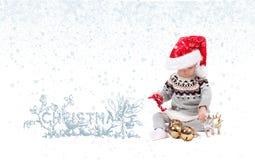 圣诞老人` s帽子的女婴有圣诞节装饰品的 冬天和雪花 免版税库存图片