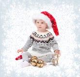 圣诞老人` s帽子的女婴有圣诞节装饰品的 冬天和雪花 图库摄影
