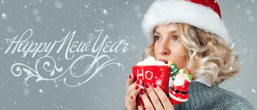 圣诞老人` s帽子的妇女喝咖啡 新年好 免版税库存图片