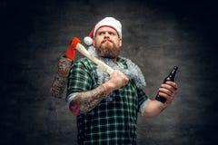 圣诞老人` s帽子饮用的啤酒的一个人 库存照片