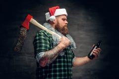 圣诞老人` s帽子饮用的啤酒的一个人 免版税库存图片