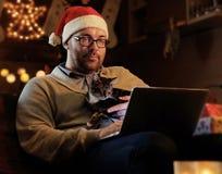 圣诞老人` s新年帽子的一个人举行一只猫和与膝上型计算机一起使用 免版税库存照片