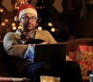 圣诞老人` s新年帽子的一个人举行一只猫和与膝上型计算机一起使用 免版税库存图片