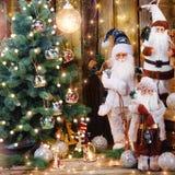 圣诞老人clouse玩偶和圣诞装饰在黑暗的土气木头 免版税库存照片