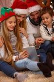 圣诞节、假日、技术和人概念家庭享用 免版税库存图片