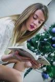 圣诞节、假日和人概念-愉快的少妇阅读书在家 有构成的愉快的美丽的性感的妇女 库存照片