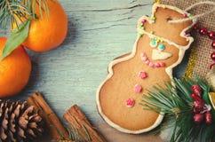 圣诞节、新年构成与姜饼人,蜜桔、杉树,杉木锥体和桂香 发光的假日 免版税库存图片