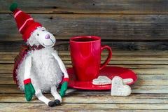 圣诞节、红色杯用咖啡和点心在木背景 库存图片