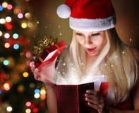 圣诞节。有圣诞老人帽子开头礼物盒的愉快的白肤金发的女孩 库存图片