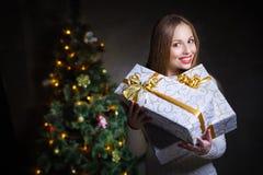 圣诞节。有许多礼物盒的微笑的妇女 免版税图库摄影