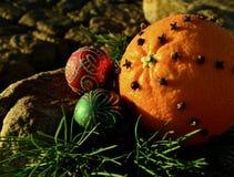 圣诞节丁香香料在7月钉牢在岩石红色和绿色闪烁装饰圣诞节的桔子 库存照片