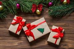 圣诞节三个箱子的礼物博览会在木背景的与杉树在屏幕的上面分支 免版税库存图片