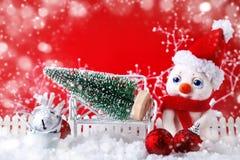 圣诞节与一个小雪人和圣诞节装饰品的冬天背景,圣诞快乐和新年快乐 免版税库存照片