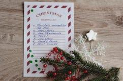 圣诞节与云杉的分支、白色雪花、银色星、装饰品和绿色五彩纸屑的购物单 免版税库存照片