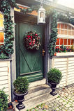 圣诞节与冷杉花圈的房子装饰在门 免版税库存照片