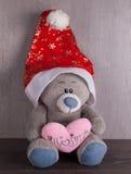 圣诞节与圣诞老人帽子的玩具熊在木背景 免版税库存照片