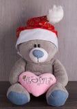 圣诞节与圣诞老人帽子的玩具熊在木背景 免版税库存图片