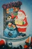 圣诞节与圣诞老人的雪球和礼物里面在白色背景 库存照片
