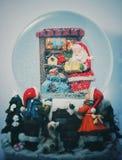 圣诞节与圣诞老人的雪球和礼物里面在白色背景 免版税库存照片
