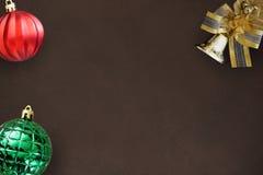 圣诞节与弓的装饰响铃,在黑暗的红色波浪和绿色有肋骨球 免版税库存图片