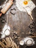 圣诞节与成份和工具的烘烤背景:曲奇饼切削刀,杯,席子,滚针,匙子 免版税库存照片
