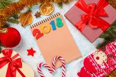 圣诞节与杉树、礼物箱子、亮晶晶的小东西、星、桂香、桔子、圣诞节袜子和棒棒糖的装饰卡片在雪backg 图库摄影