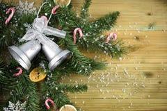 圣诞节与树枝的摄影图片和银色颜色响铃装饰棒棒糖和结果实所有洒与雪 免版税库存图片