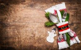 圣诞节与欢乐装饰、餐巾、利器和雪人的桌设置在土气木背景,顶视图 免版税库存图片