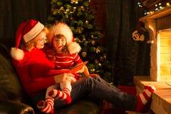 圣诞节与母亲和孩子的故事时间 免版税库存图片