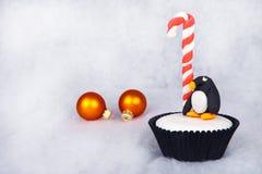 圣诞节与白色方旦糖结霜的企鹅杯形蛋糕 免版税库存图片