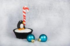 圣诞节与白色方旦糖结霜的企鹅杯形蛋糕 免版税库存照片
