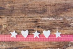 圣诞节与白色星和心脏的贺卡装饰在红色丝带边界和木头背景 免版税库存图片