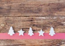 圣诞节与白色星和树装饰品的贺卡装饰在红色丝带边界和木头背景 免版税图库摄影