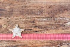 圣诞节与白色星的贺卡装饰在红色丝带边界和土气木背景 库存照片
