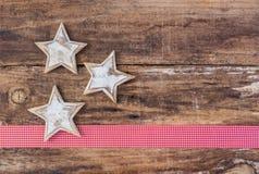 圣诞节与白色星装饰品、红色丝带边界和木头背景的贺卡装饰 库存图片