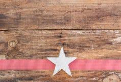 圣诞节与白色星装饰品的贺卡装饰在红色丝带边界和木头背景 图库摄影