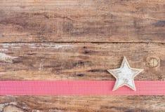 圣诞节与白色星装饰品的贺卡装饰在红色丝带边界和木头背景 免版税图库摄影