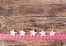 圣诞节与白色星装饰品的贺卡装饰在红色丝带边界和木头背景 免版税库存照片